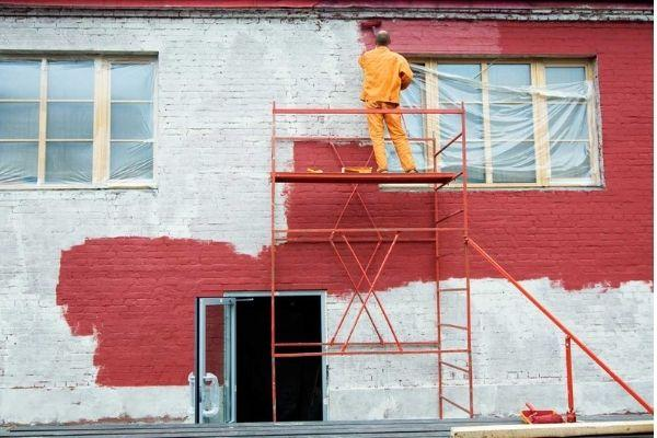 exterior brick painter with ladder and red paint