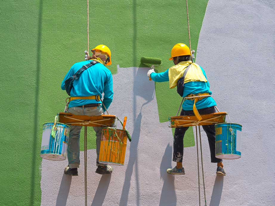 two strata painters with brushes abseiling on building